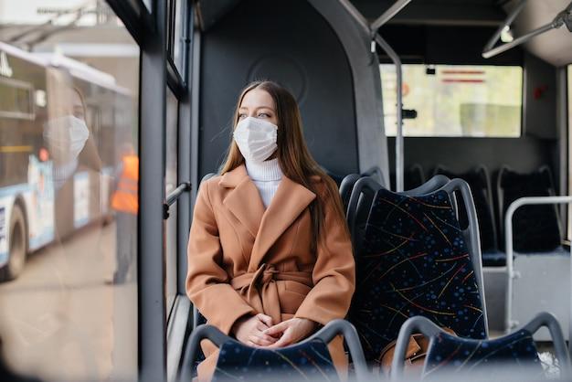 仮面の少女は、パンデミックの最中に一人で公共交通機関を利用しています。保護と防止のcovid 19。