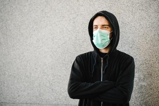 コロナウイルス。灰色の壁に医療用防護マスクを着た男。 covid-19、インフルエンザを防ぎます。街の気分が悪い。人は助けを必要としています。ウイルス、パンデミック、パニックの概念。