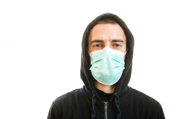 コロナウイルス。白い壁に医療用防護マスクを着た男。 covid-19、インフルエンザを防ぎます。ウイルス、パンデミック、パニックの概念。健康を守ります。検疫の概念。テキストのためのスペース。