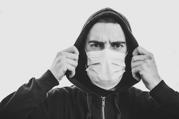 コロナウイルス。壁に医療用防護マスクを着た男。 covid-19、インフルエンザを防ぎます。街の気分が悪い。人は助けを必要としています。ウイルス、パンデミック、パニックの概念。黒と白の写真。