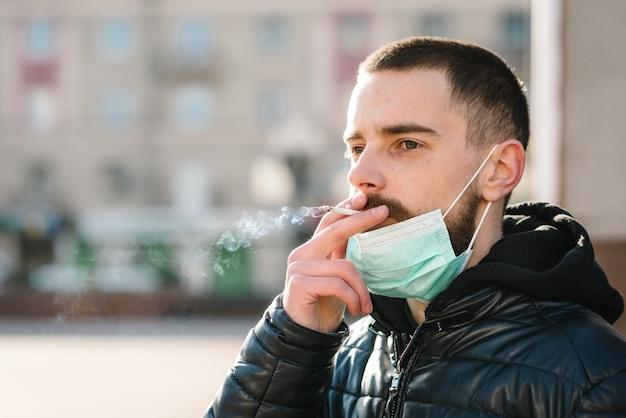 コロナウイルス。喫煙。通りでタバコを吸ってcovid-19パンデミック中にマスクを持つクローズアップ男。喫煙は肺がんやその他の病気を引き起こします。喫煙の危険性と害。