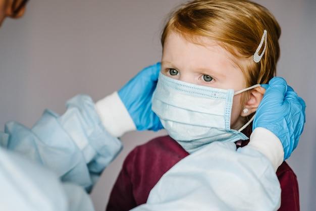 コロナウイルス。看護師、防護服の医者は、子供のために顔に医療マスクを置きます。 covid-19感染に対する予防策。インフルエンザ、コロナウイルスの流行に対する保護の概念。