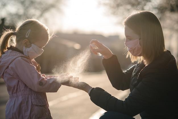 Коронавирус. женщина в защитной маске пользуется спреем-дезинфицирующим средством на руках ребенка на улице. профилактические меры против инфекции covid-19. антибактериальный спрей для мытья рук. защита от болезней.