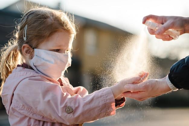 コロナウイルス。女性は、路上の防護マスクで子供の手にスプレー消毒剤を使用します。 covid-19感染に対する予防策。抗菌手洗いスプレー。病気からの保護。