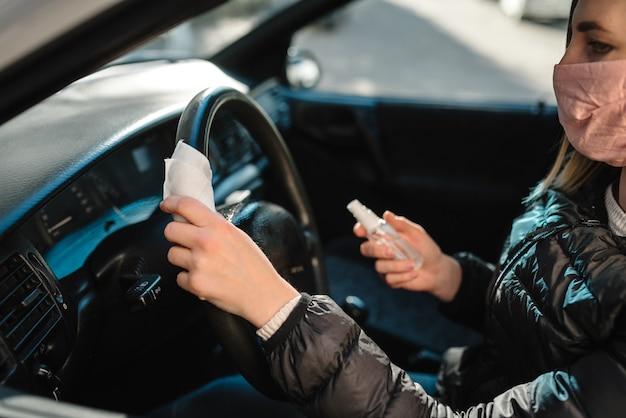 ワイプの消毒。ステアリングホイール車、感染制御の概念に抗菌消毒スプレーをスプレーします。コロナウイルス、covid-19、インフルエンザを予防します。車を運転して医療用防護マスクを着ている女性。