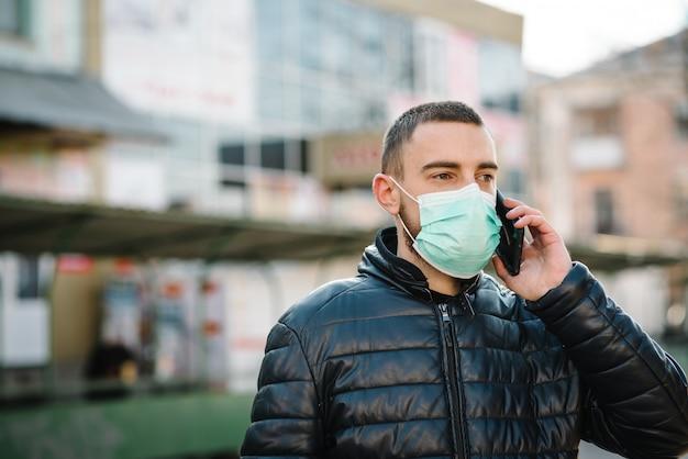 コロナウイルス。通りを歩いて医療用防護マスクを着用し、携帯電話で話している人。 covid-19、インフルエンザを防ぎます。街の気分が悪い。人は助けを必要としています。ウイルス、パンデミック、パニックの概念。