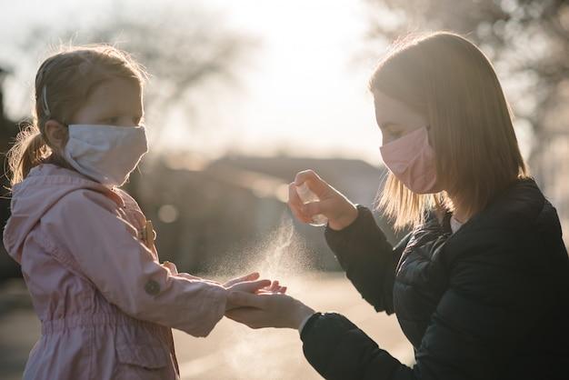 コロナウイルス。防護マスクの女性は、路上の子供の手にスプレー消毒剤を使用します。 covid-19感染に対する予防策。抗菌手洗いスプレー。病気からの保護。
