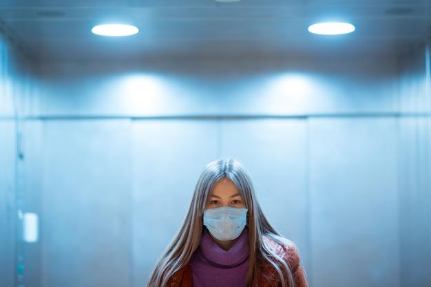 医療マスクのエレベーターに立っている若いアジア女性。コロナウイルスcovid-19パンデミックのコンセプト。