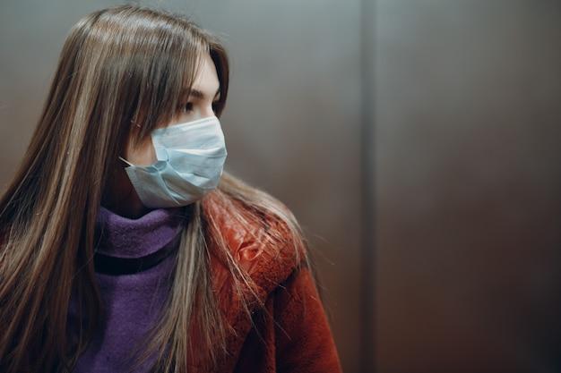 医療マスクのエレベーターに立っている若い女性。コロナウイルスcovid-19パンデミックのコンセプト。
