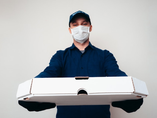 Covid-19パンデミックで青いシャツ、キャンプ、マスク、手袋を着用したフードデリバリーサービスワーカー。