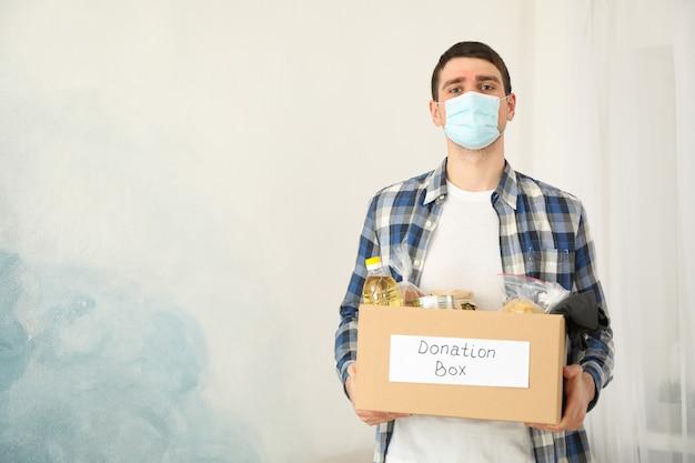 若い男は募金箱を保持しています。ボランティア。 covid 19