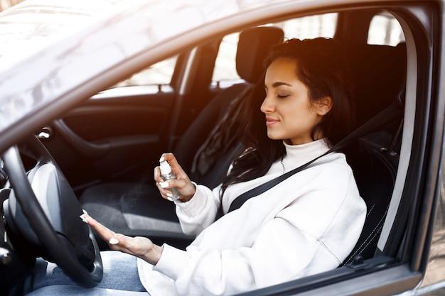 手のクローズアップ。女性が車の中で手指消毒剤を使用しています。ウイルスやバクテリアから保護します。女性モデルはコロナウイルスcovid-19の病気を望まない