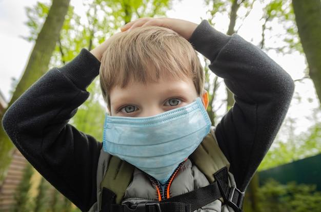 Симпатичный четырехлетний мальчик гуляет в парке ранней весной в медицинской маске из-за пандемии короновируса (covid-19).