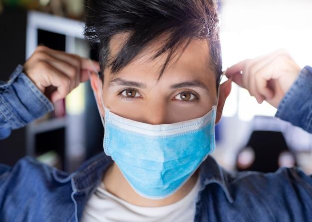 Уверен молодой врач хирург с медицинской маской на лице. профессиональный доктор человека надел защитную маску. личная защита. коронавирус (covid-19