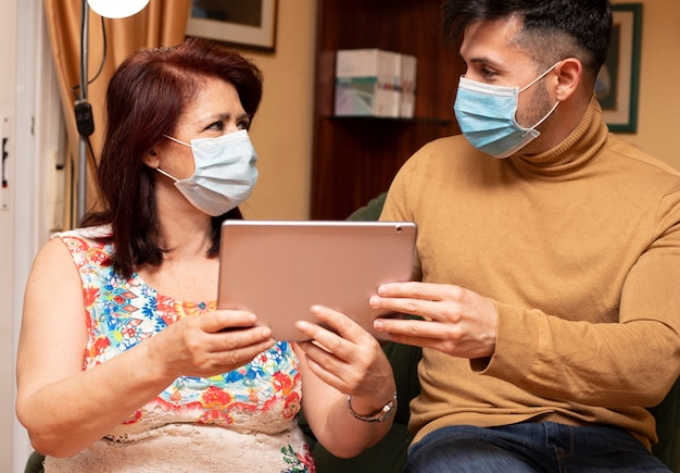 Сын помогает матери использовать планшет. пожилые люди, использующие технологию носите пандемические маски для лица. covid-19