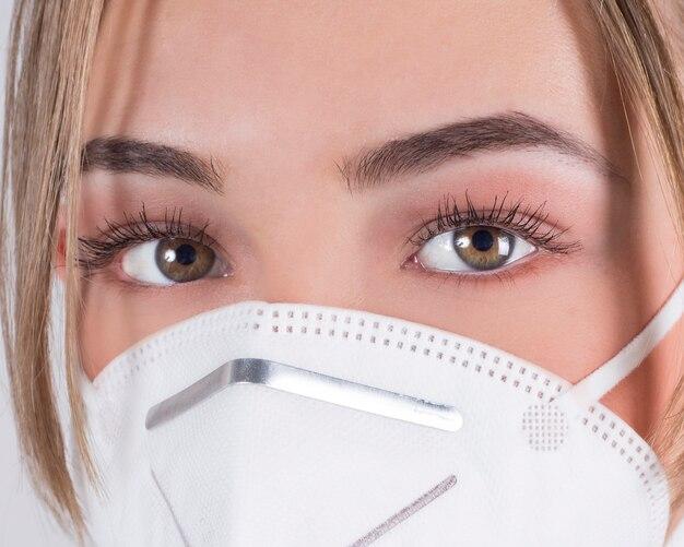 白い壁に医療マスクを持つ女性医師のクローズアップ。 covid-19
