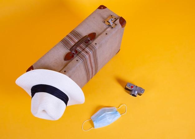 Медицинская маска, путешествия, самолеты, чемодан, фотоаппарат, желтый фон, проблемы с путешествиями по covid-19