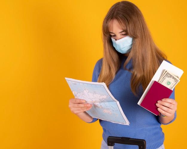 Девушка-туристка с медицинской маской, с чемоданом, с паспортом, билетами на самолет и картой, ваш рейс был отменен covid-19