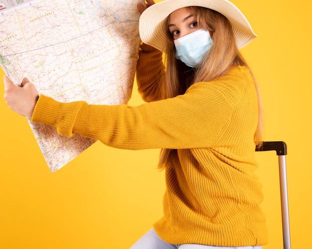 Девушка-туристка в медицинской маске, с чемоданом, в шляпе со справочной картой, рейсы отменены covid-19