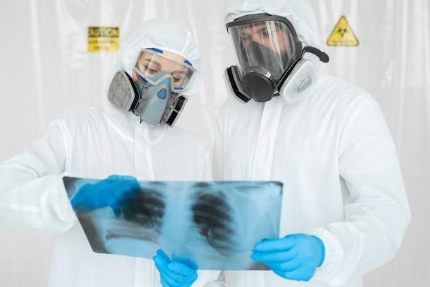 Эпидемиологи в респираторах осматривают пневмонию больного на рентгенограмме covid-19. концепция коронавируса