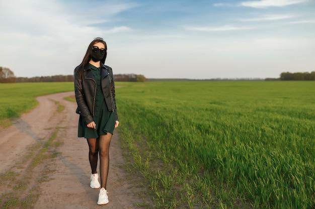 マスクの少女は、緑のフィールドで実行または歩く。検疫春夏。コロナウイルス。 covid 19。