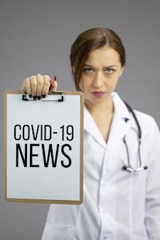 怒っている女性看護師はクリップボードcovid-19ニュース、コロナウイルスの静的な概念を示しています
