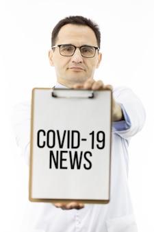 Covid-19ニュースの碑文と医師表示クリップボード。コロナウイルスパンデミック