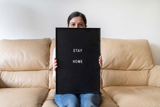 Covid 19ウイルス性疾患のパンデミック発生中に家にいるようにというメッセージが表示された空の黒板を保持している健康な女性。感染を避けるための予防策のリスト。コロナウイルスの概念。
