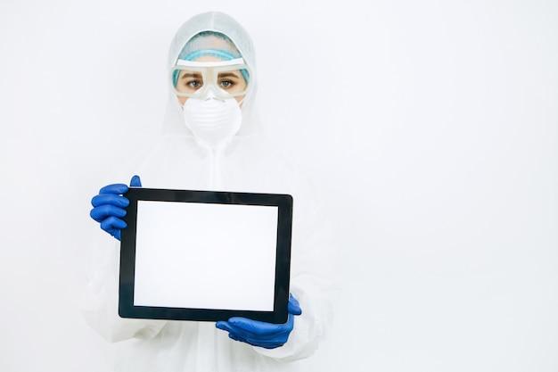 防護服、防毒マスク、メガネ、手袋の医師は、タブレットを保持しています。医師たちはコロナウイルスの流行中は家にいるように勧めた。 covid-19