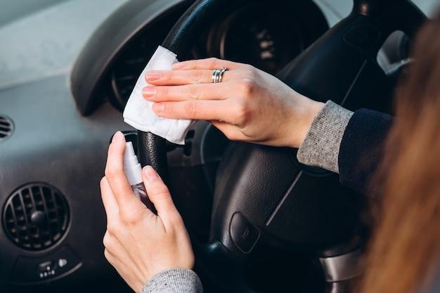 女性は車を運転中に消毒剤を使用します。コロナウイルス流行時の注意事項。 covid-19のヒューズ。車の中で医療マスクの女の子。