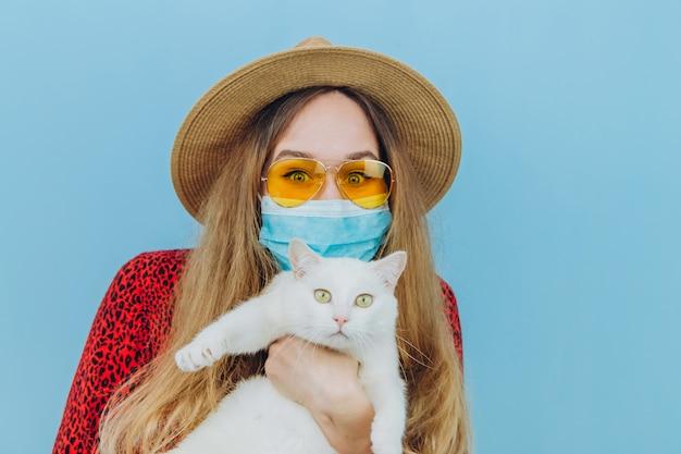 Девушка в платье, шляпу и солнцезащитные очки с медицинской маской на лице. каникулы при эпидемии коронавируса. самоизоляция с домашними животными. девушка держит в руках белого кота. covid-19