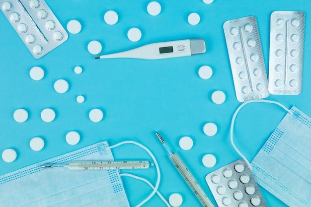 薬、薬、注射器、温度計、青いテーブルの上の医療用マスクとバイアル。季節性インフルエンザと風邪の治療法。 covid-19の治療のための手段。テキストのための場所。コロナウイルス