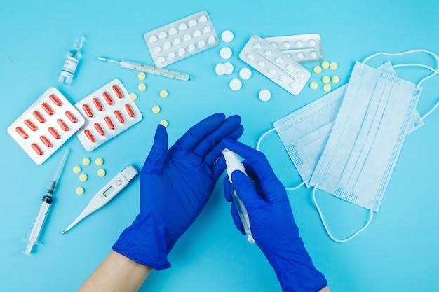 青い手袋で医師の手。コロナウイルスのための薬。 covid-19との戦いにおける医薬品。薬、注射器、温度計、青いテーブルに医療マスク。