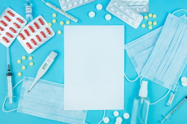 青い手袋で医師の手。コロナウイルスのための薬。 covid-19との戦いにおける医薬品。薬、注射器、温度計、青いテーブルに医療マスク。テキストのための場所。上面図