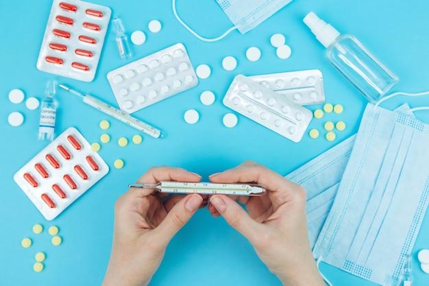 医者の手は薬を持っています。コロナウイルスの治療法。 covid-19との戦いにおける医療救済。薬、注射器、温度計、青いテーブルに医療マスク。