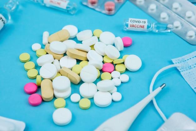 コロナウイルスの薬。 covid-19との戦いにおける医薬品。薬、注射器、温度計、青いテーブルに医療マスク。 。