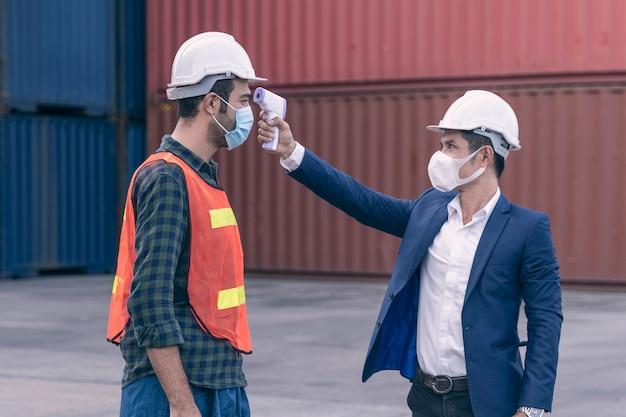 Персонал проверяет лихорадку у посетителя цифрового термометра, прежде чем приступить к работе для сканирования и защиты от коронавируса или covid-19