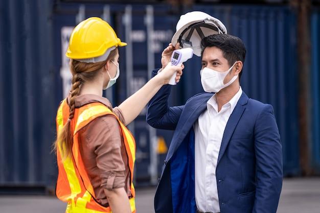 Вирус covid 19 кризис персонал проверяет лихорадку у посетителя цифрового термометра перед тем, как войти в работу для сканирования и защиты от коронавируса