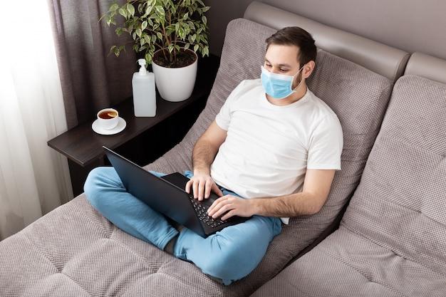 在宅勤務。ラップトップを使用して自宅で働いて顔サージカルマスクの男フリーランサー。ソファの上の居心地の良いホームオフィス。コロナウイルスcovid-19社会的隔離自己検疫
