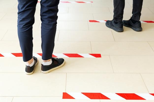 人々は社会的距離を保って並んで立っており、covid 19コロナウイルスの検疫中に警告線の後ろに立っています