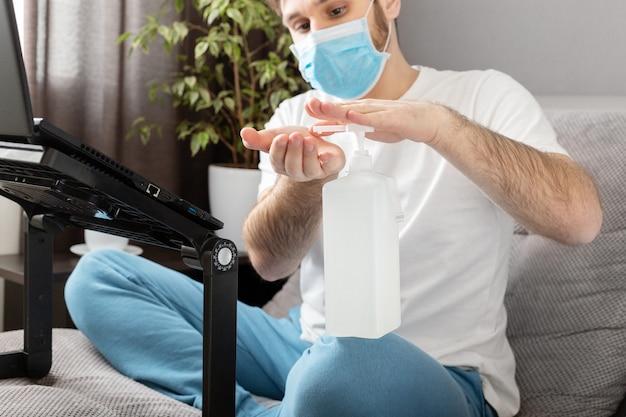Человек использует дезинфицирующее средство для очистки рук. коронавирус covid 19 защита, гигиена рук. фрилансер в лице хирургическая маска. удаленная работа.