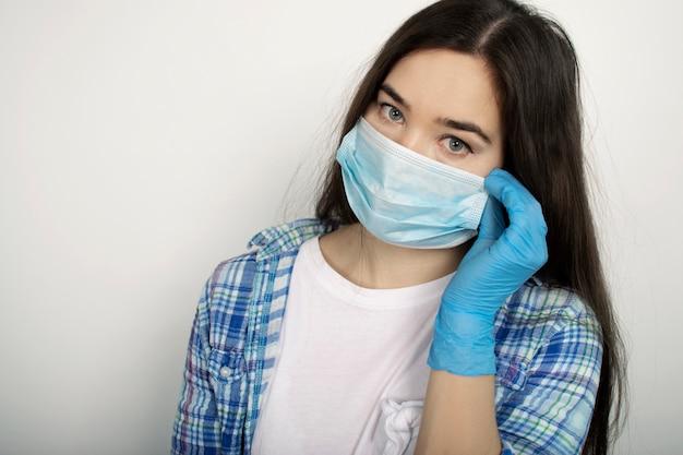青い医療マスクと手袋で孤立した背景の女の子。ウイルス、インフルエンザ、コロナウイルスの使い捨て治療。パンデミックアウトブレイク。 covid-19(新型コロナウイルス感染症)(#文字数制限がない場合、初出時にかっこ書きを追加