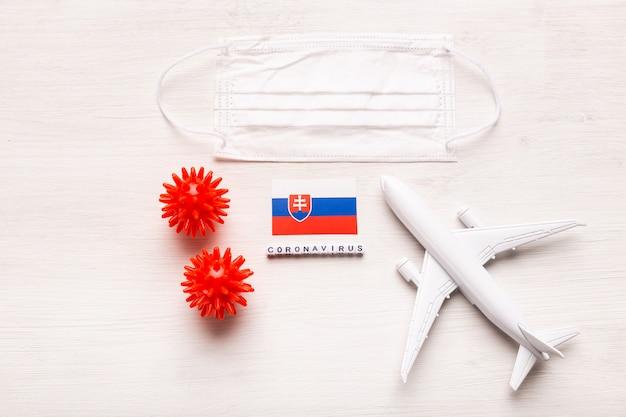 飛行機モデルとフェイスマスクとスロバキアの旗。コロナウイルスパンデミック。ヨーロッパとアジアからのコロナウイルスcovid-19による旅行者と旅行者のための飛行禁止と閉鎖国境。