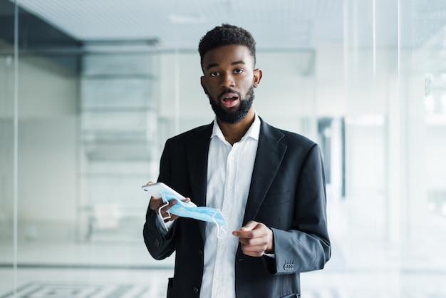 コロナウイルスから保護するための医療用マスクまたはオフィスでcovid-19を持つアフリカの実業家