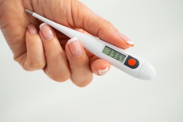 手が温度計を持っています。コロノウイルスcovid-19の兆候としての発熱