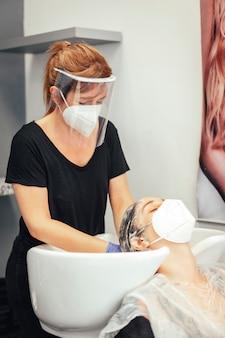 マスクと手袋で美容師がクライアントの髪を石鹸で洗います。 covid-19パンデミックにおける美容院のセキュリティ対策を再開