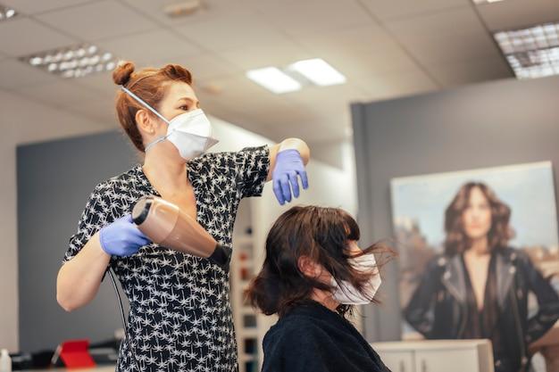 Covid-19、新しい正常性、社会的距離のためのセキュリティ対策を備えた美容院。マスクでブルネットのクライアントの髪を乾かす