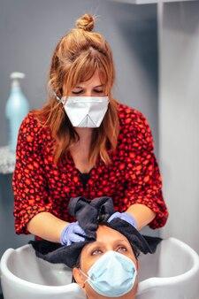 マスクと手袋を備えた美容師がタオルでクライアントの髪を乾かします。 covid-19パンデミックにおける美容院のセキュリティ対策を再開