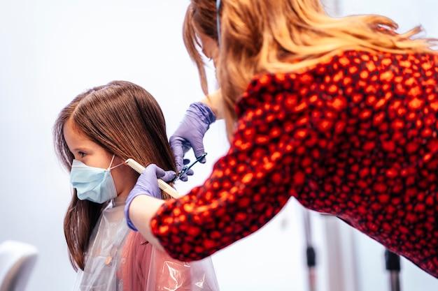 はさみで女の子の髪を切るマスクと手袋の美容師。 covid-19パンデミックにおける美容院のセキュリティ対策を再開