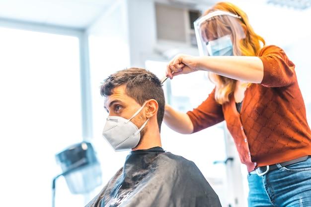 コロナウイルス大流行後の美容院。フェイスマスクと保護スクリーンを備えた美容師、covid-19。社会的距離、新しい正常性。美容院で若い男